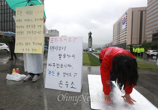 """""""도와주세요"""" 대 """"표 구걸??"""" 6.4지방선거를 하루 앞둔 3일 오후 손수조 새누리당 당협위원장이 서울 광화문광장에서 '도와주세요! 머리부터 발끝까지 바꾸겠습니다. '부산'을 믿어요! 손수조'가 적힌 피켓을 놓고 절을 하고 있다. 옆에서는 '중·고생 엄마'라고 밝힌 시민이 '오늘 세월호 49재. 세월호 아이들이, 유가족들이 살려달라 울부짖을 때 당신들은 도와주었나요? 도와주세요?? 표 구걸?? 16명의 실종자 찾아주세요'가 적힌 피켓을 들고 1인 시위를 하고 있다."""