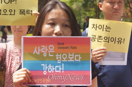"""대구여성인권센터 한 회원이 25일 오전 열린 대구퀴어문화축제 지지선언에서 """"사랑은 혐오보다 강하다""""라고 쓴 피켓을 들고 서 있다."""