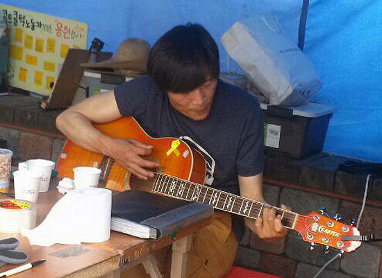 """기타 연주하는 이인근 지회장 이인근 지회장은 """"실력이 늘지 않는다""""며 웃었다. 그러나 그는 지나치게 겸손했다. 그의 기타 실력은 수준급이었다."""