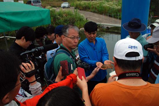 환경운동연합 염형철 총장이 함안보 선착장에서 발견한 큰빗이끼벌레를 들어 보이자 취재진이 몰렸다. 정민걸 교수(왼쪽 안경 쓴 인물)가 설명하고 있다.