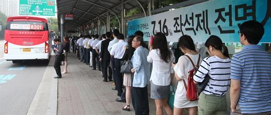 경기도와 서울 간 고속화도로를 지나는 직행좌석형(빨간색) 광역버스의 입석 운행 금지 첫날인 지난 16일 오전 경기도 용인 지역난방공사 좌석제 시행을 알리는 현수막 앞에서 출근길 시민들이 광역버스에 오르고 있다. 경기도는 입석 운행 금지에 따른 승객 불편을 막기 위해 188대의 버스를 늘려 이날 출근길 혼란은 없었다. 사진 오른쪽 긴 줄은 직행 좌석형 광역버스(M버스)를 타기 위한 것.