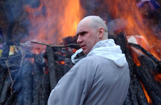 활활 타오르고 있는 연화대 앞에서 고뇌에 찬 모습을 보이고 있는 서양인 스님