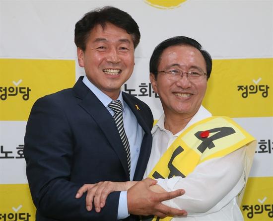 서울 동작을 야권 단일후보가 된 정의당 노회찬 후보(오른쪽)가 24일 서울 동작구 사당동 선거사무소에서 이날 후보직을 사퇴하고 방문한 새정치민주연합 기동민 후보와 포옹하고 있다.
