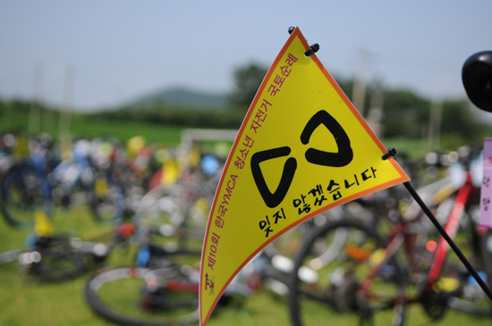 노란 깃발 청소년 아이들이 자전거에 깃발을 매달고 달리고 있습니다.