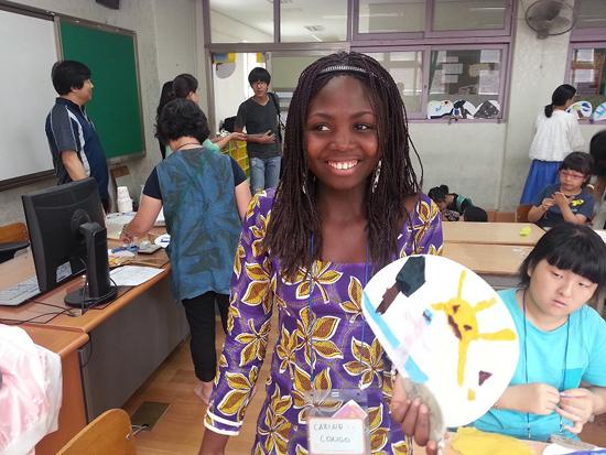 아프리카 콩고 소녀 카리네 경기도 광명시민체육관과 하안북초등학교에서 진행되는 세계대안교육대회에서 한국의 문화 방에서 부채를 만들고. 부채에 태양, 나무, 나비를 담았다.