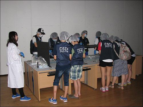 CSI 프로파일링 체험전 루미놀을 이용한 혈흔반응 실습을 하고있는 참가자들