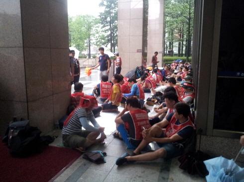 8월 6일, 비가 내리는 가운데 비를 피해 서울파이낸스센터 입구 주변에 모인 노조 조합원들