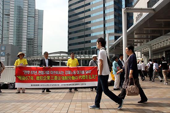 일본 시민단체 '나고야 소송 지원회' 회원들이 동경 시내에서 출근길 시민들을 상대로 미쓰비시의 사죄를 촉구하는 선전활동을 펼치고 있는 가운데 시민들이 무심히 지나가고 있다. 2012년 8월 10일