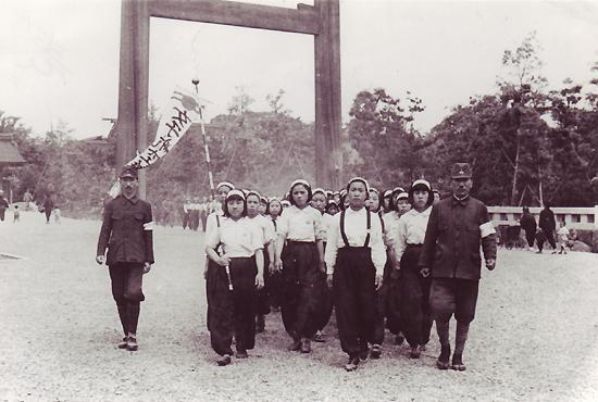 """""""일본에 가면 돈도 벌고 공부도 가르쳐 준다""""는 일본인 담임선생의 말에 속아 불과 13~15세 어린 나이에 미쓰비시중공업 군수공장으로 동원된 소녀들이 일본인 인솔자에 이끌려 신사참배에 나선 모습. 1944년 6월경."""