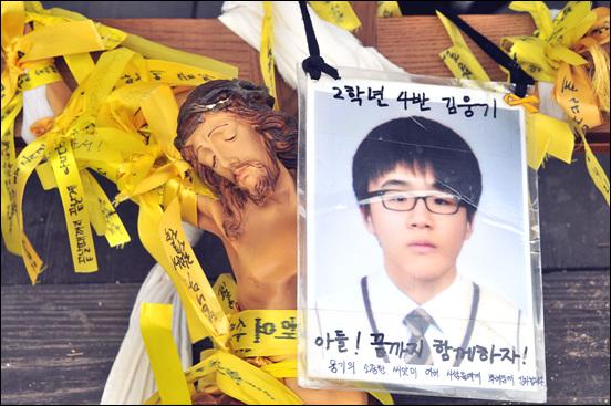 800km 십자가 도보순례단이 메고 온 십자가. 십자가에 단원고 2학년 4반 故 김웅기 군의 학생증이 걸려 있다.