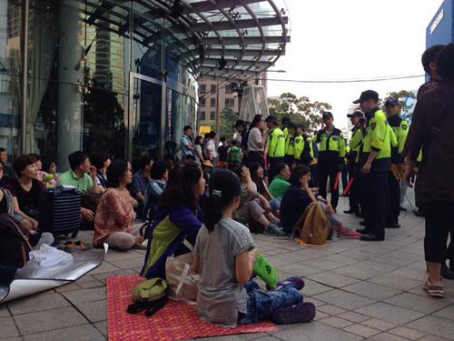 경찰이 와서 시민들에게 일어나라고 말하고 있다.
