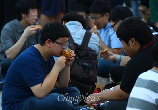 일베 회원등이 세월호 진상규명 특별법 단식농성장 앞에서 '도시락 나들이' 등 먹거리 집회를 예고한 6일 오후 서울 광화문광장 세종대왕상 앞에서 일베 회원들과 시민들이 피자와 치킨을 먹고 있다.