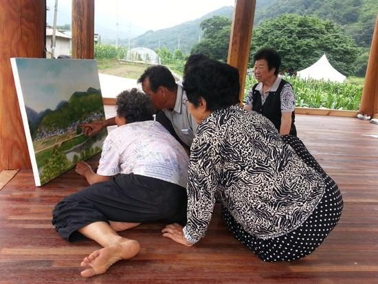 '1998 진뫼마을의 봄' 구경하는 마을 사람들 그림을 보며 '우리집은 어디에 있데아' 마을 사람들 가르키고 있다.  그림 정종임