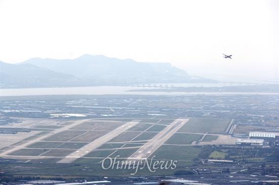 김해 신어산 정상에서 바라본 김해공항 전경으로, 멀리 낙동강 하구언도 보인다.