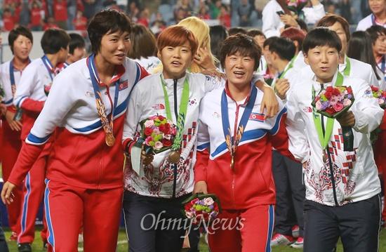 어깨동무한 남북한 여자축구 선수들 1일 오후 인천 문학월드컵경기장에서 열린 '2014 인천아시아경기대회' 여자축구 시상식에서 금메달을 획득한 북한 축구대표팀 선수들과 동메달을 획득한 한국 축구대표팀 선수들이 어깨동무를 하고 그라운드를 나서고 있다.