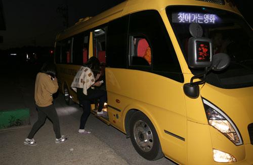 비금중학교 학생들이 '찾아가는 영화관'이 들어선 비금초등학교로 가기 위해 마을 앞에서 시네마 버스에 오르고 있다.