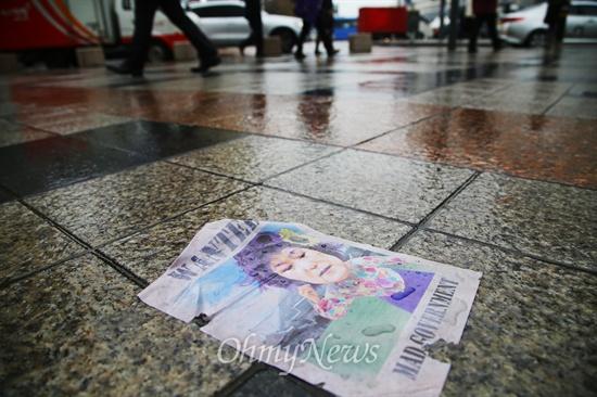 팝아트 작가 이하씨가 20일 오전 서울 종로구 동화면세점 옥상에 살포한 박근혜 대통령 풍자 '삐라'가 비에 젖은 채 바닥에 떨어져 있다.