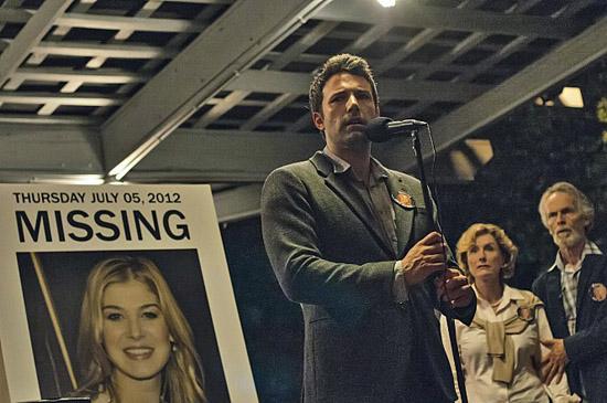 실종된 에이미(로자먼드 파이크)를 찾는다는 게시물 앞에서 이야기를 하고 있는 닉(벤 애플랙)