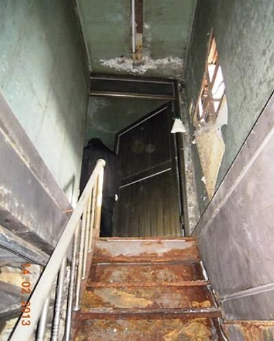 군산 개복동 화재 현장 사진. 10년이 넘은 상태로 방치되어 있었던 내부 모습으로 녹슨 철제 계단 위로 보이는 철제문이 2층 출입문이다. 화재 당시 잠겨진 상태였고, 2층은 주택으로 신고된 곳인데 영업장이었다. 옆벽의 베니어합판을 뒤로 보이는 빈 공간이 밖에서 보면 유리창으로 보이는 곳이다.