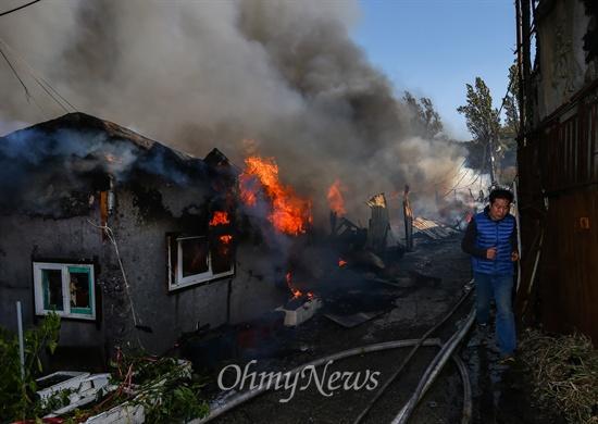 불길 옆 지나가는 구룡마을 주민 9일 오후 서울 강남구 구룡마을 7-B지역에서 화재가 발생해 주민들이 대피하고 있다.