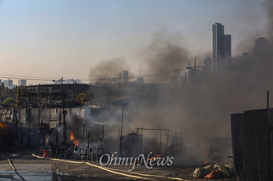 9일 오후 서울 강남구 구룡마을 7-B지역에서 화재가 발생해 소방관들이 화재 진압을 하고 있다. 마을 넘어로 강남의 고층 빌딩이 보이고 있다.