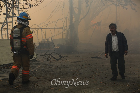 불탄 마을이 걱정인 마을 주민 9일 오후 서울 강남구 구룡마을 7-B지역에서 화재가 발생해 화재 진압 중인 소방관 옆을 한 주민이 지나고 있다.