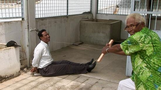 영화 <액트 오브 킬링>의 한 장면. 대학살의 주범 '안와르 콩고(사진 속 오른쪽)'는 천연덕스럽게 웃으며 당시 살해방법을 재연한다.