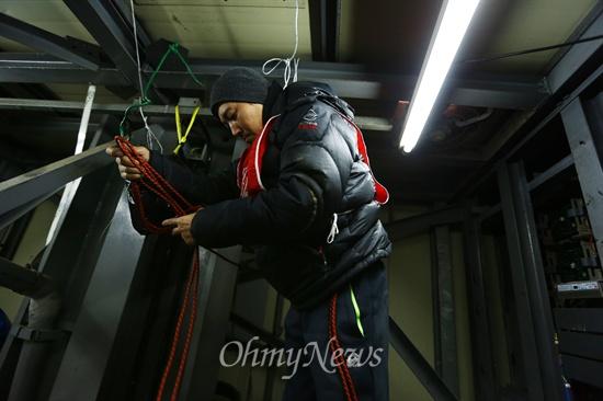 흔들리는 30미터 탑위에서 유일하게 의지 할 수 있는 로프를 몸에 묶고 있다.
