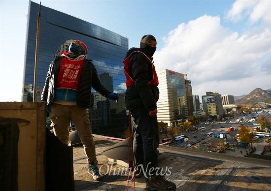 고공농성을 하며 광고탑 위에 선 해고노동자 강성덕씨(왼쪽)와 조합원 임성준씨.