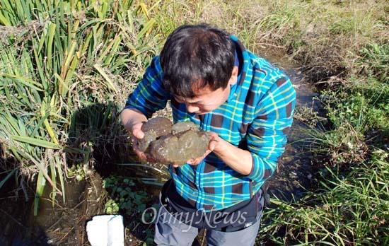 공주보 앞에서 큰빗이끼벌레를 건진 뒤 냄새를 맡아보는 김종술 시민기자.