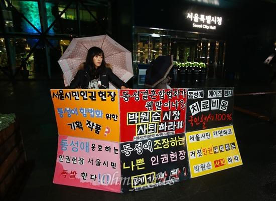 서울시민인권헌장 제정 시민위원회 최종 회의가 열리는 28일 오후 서울 시청사 주변에서 인권헌장 제정을 반대하는 시민들이 피켓을 들고 시위를 하고 있다.
