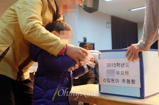4일 서울 영등포구의 한 유치원에서 한 어린이가 보호자와 함께 입학 추첨을 하고 있다.