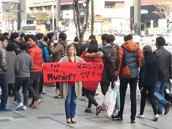 강남 한복판에서 모피반대 캠페인을 진행하고 있는 캐서린 버나드-김씨 미국인 캐서린 버나드-김 씨가 강남 한복판에서 'Fur is Murder. 모피는 잔인한 살생입니다'라는 문구가 적힌 현수막을 들고 서 있다.