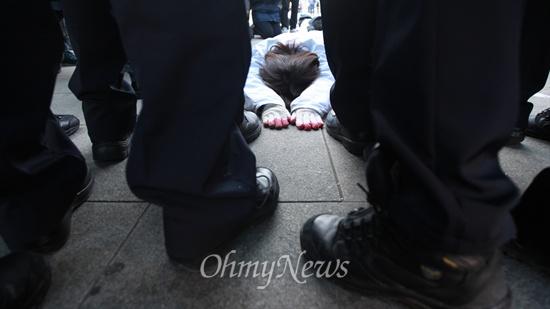 """금속노조 기륭전자분회 조합원들과 연대단체 참석자들이 26일 서울 종로구 광화문광장에서 고용불안에 시달리는 비정규직의 고통을 알리기 위해 오체투지를 벌이며 청와대 앞에서 기자회견을 진행하려 했으나 경찰의 저지에 막혀 무산됐다. 이날 이들은 """"낮은 자세로, 온몸으로 기어 비정규직의 현실을 알리려 했지만 이마저도 허용되지 않았다""""며 """"흙먼지를 뒤집어써서 거지꼴이 된 우리의 모습이 2014년을 사는 한국 비정규직의 모습""""이라고 말했다."""