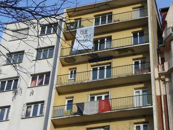 한 건물에 내걸린 피켓('샤를리가 살아남길 바란다'라는 뜻)과 아래 층에 걸린 프랑스 국기.