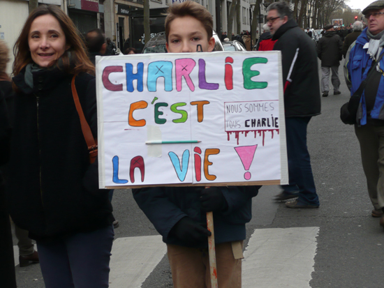 한 소년이 '샤를리는 인생이다'라고 적힌 피켓을 들고 있다.