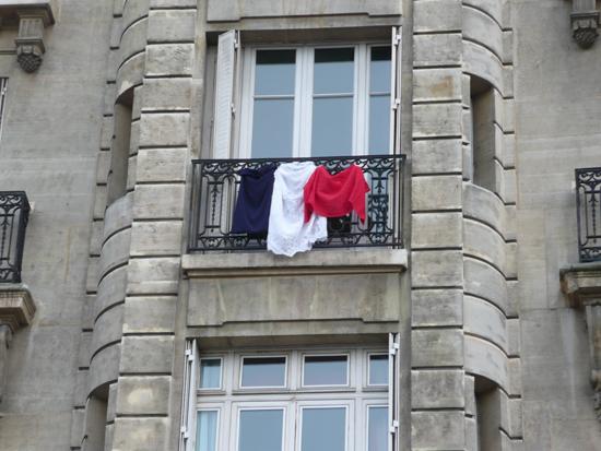 한 건물에 흰색 속치마와 푸른 티셔츠, 빨강 스카프로 연출한 독특한 프랑스 국기가 걸려있다.