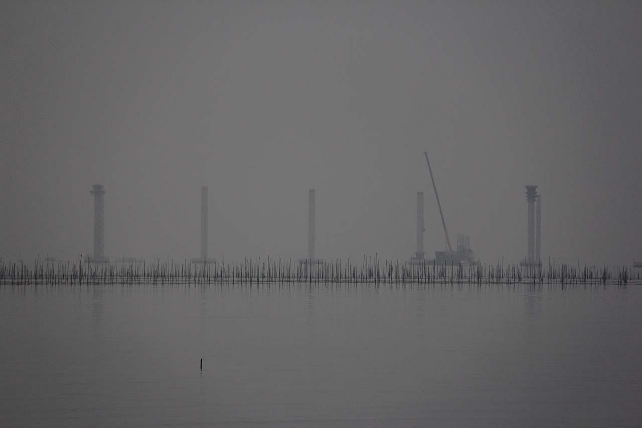 김양식을 하기 위해 바다에 세운 지줏대 너머로 연륙교 공사가 한창이다.