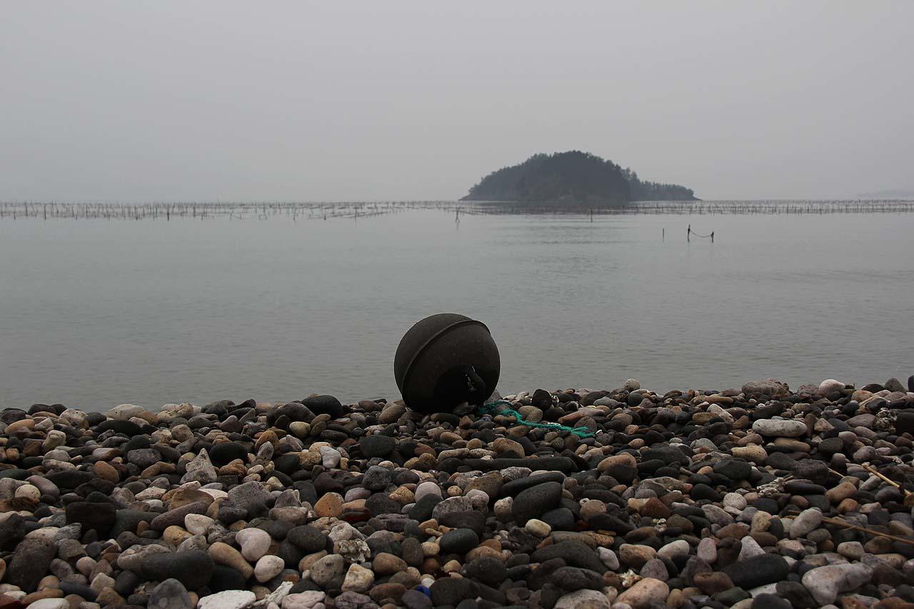 당사도 작지의 자갈은 작고 부드러웠다. 작지에 밀려온 부표 너머로 김 양식장과 섬이 보인다.