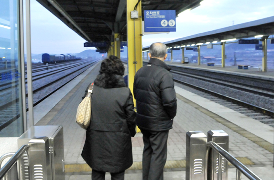 신례원역을 찾은 두 어르신이 추위를 피해 에스컬레이터 통로에서 기차를 기다리고 있다.