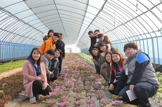 젊은협업농장 쌈채소 하우스에서 조대성 대표와 대산농촌재단 장학생들이 환하게 웃고 있다.
