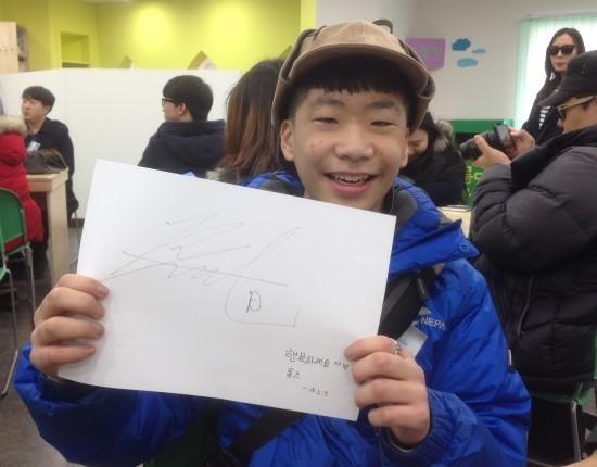 최연소 참가자 박우빈군이 카페장인 노영욱씨의 사인을 받고 환하게 웃고 있다.