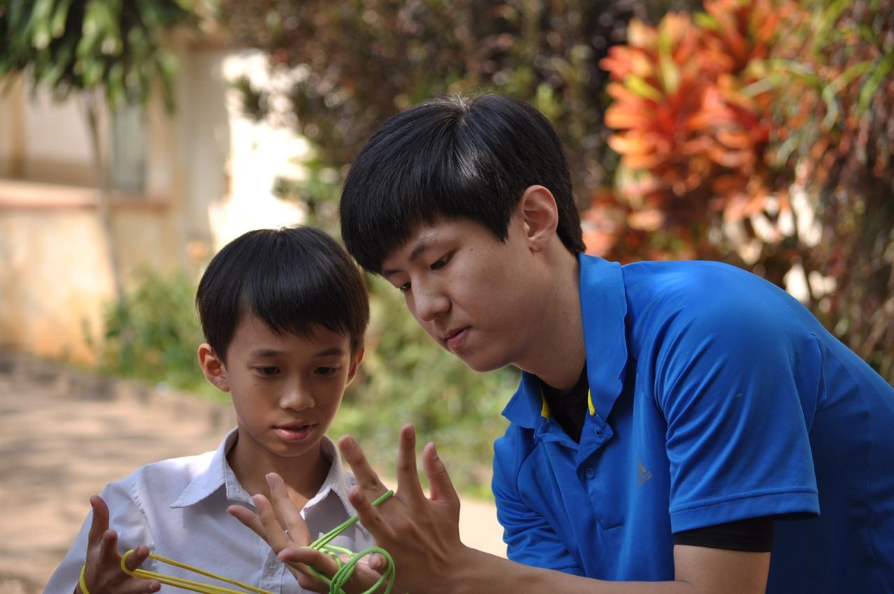 빈호아 초등학교 아이들에게 실뜨기 놀이를 알려주고 있다.