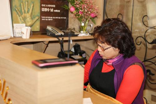김경수씨의 부인 차정례씨. 점심 손님맞이를 끝낸 차씨가 카운터에 앉아서 휴대폰을 검색하고 있다.