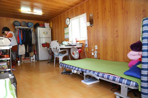 반승환 씨의 컨네이너 집 내부. 간이 침대와 냉장고, 플라스틱 탁자가 놓여 있다. 그의 부인 강경녀 씨가 점심식사를 준비하고 있는 모습이다.