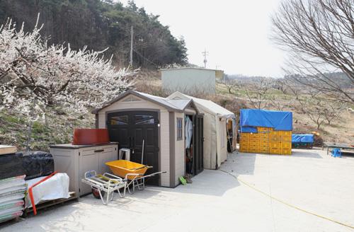 반승환 씨의 집앞에 자리잡은 자재창고. 천막 등으로 비를 피할 수 있게 만들어 놓았다.
