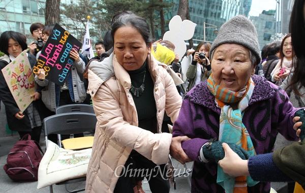 수요집회 참석한 베트남전 민간인학살 피해자 8일 오후 서울 종로구 일본대사관 앞에서 열린 '일본 위안부 문제 해결을 위한 1173차 수요집회'에 참석한 베트남전 한국군 민간인학살 피해자 응우옌 티 탄(NGUYEN THI THANH) 씨가 길원옥 할머니를 부축하며 길을 안내하고 있다.