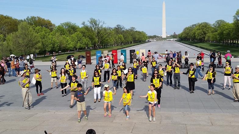 """세월호 참사 1년 워싱턴 행사 워싱턴 미시맘이 주관한 링컨 광장에서 참여자들이 """"진실은 침몰하지 않는다' 노래에 맞춰 율동을 하고 있다."""