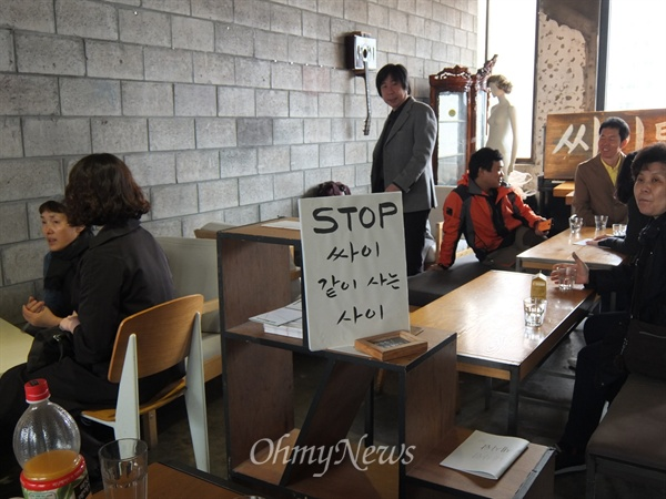 """카페 드로잉 안 곳곳에는 """"같이 살자, 한남동 카페 데이크아웃드로잉은 싸이건물에서 쫓겨나게 됐어요, 임대차보호법이 바뀌어야 합니다""""라 쓰인 팻말이 있었다. 이날 오전, 명도집행 소식을 듣고 이를 막기 위해 한달음에 달려온 지인들도 20여명 정도 있었다."""