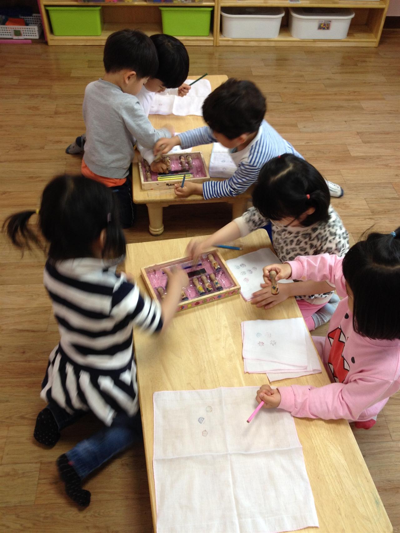 손수건에 도장찍기 놀이를 하고 있다. 30분짜리 프로그램으로 준비했으나 10분이 지나자 아이들은 다른 놀이를 하고 싶어 했다.